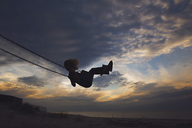 Side view of girl playing on swing at beach against cloudy sky during sunset - CAVF15645