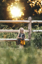 Cheerful girl with camera standing on grassy field against fence during sunset - CAVF15648