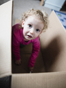 Portrait of playful girl sitting in cardboard box at home - CAVF15660
