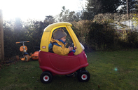 Girl driving toy car on grassy field in backyard - CAVF15678