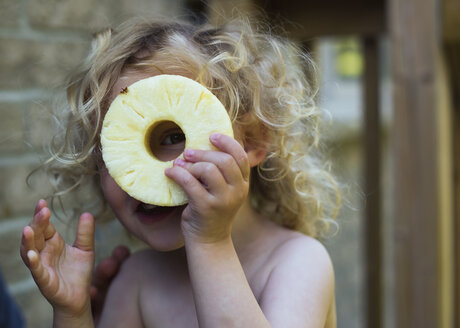 Portrait of playful girl looking through pineapple slice at home - CAVF15801