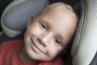 Portrait of happy boy sitting in vehicle - CAVF15807