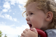 Close-up of cute girl shouting at playground against sky - CAVF15810