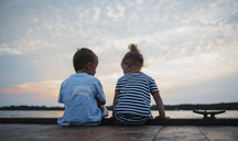 Rear view of siblings sitting on pier against cloudy sky during sunset - CAVF15828