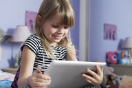 Low angle view of happy girl using digital tablet in bedroom - CAVF15858