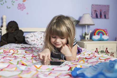 Close-up of smiling girl using digital tablet while lying on bed - CAVF15864