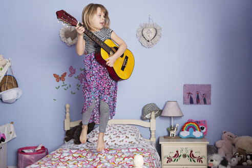 Girl holding guitar and jumping on bed - CAVF15867