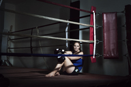 Tired sportswoman sitting in boxing ring at gym - CAVF15876