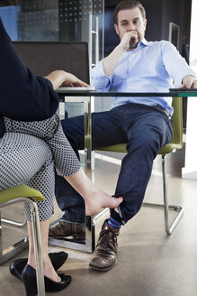 Low section of businesswoman playing footsie with male colleague at conference table - CAVF15936