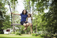 Sisters playing on swing at park - CAVF15996