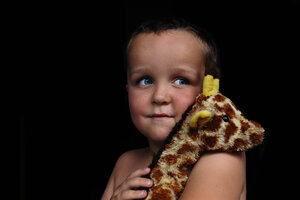 Thoughtful shirtless boy looking away while holding toy against black background - CAVF16020