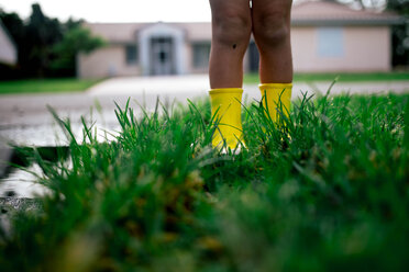 Low section of boy standing on wet grassy field during rainy season - CAVF16029