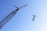 Low angle view of crane carrying ladder against clear blue sky - CAVF16053