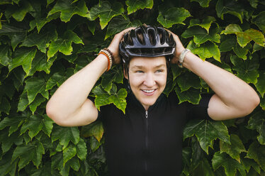 Smiling male cyclist wearing helmet against ivy - CAVF16083