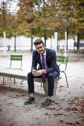 Portrait of smiling businessman sitting at park bench - CAVF16134