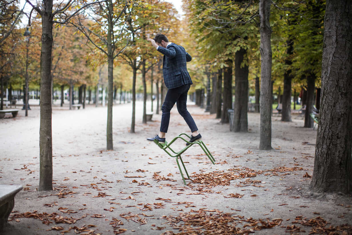 Full length of businessman playing on chair at park - CAVF16137 - Cavan Images/Westend61