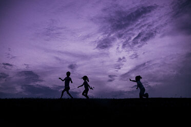 Happy sisters playing on field against dramatic sky during sunset - CAVF16200