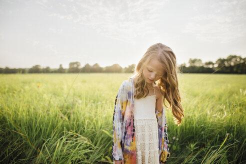Sad girl standing on grassy field against sky - CAVF16203