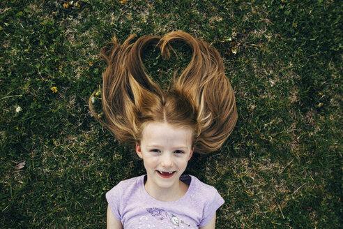 Portrait of happy girl lying on field - CAVF16206