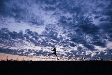 Silhouette girl jumping on field against dramatic sky - CAVF16209