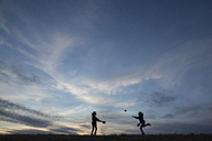 Silhouette sisters playing with ball on field against sky - CAVF16218