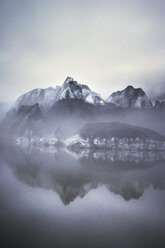 Scenic view of mountain by lake in foggy weather - CAVF16278