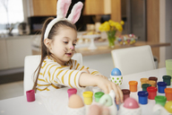 Girl with bunny ears sitting at table painting Easter eggs - ABIF00163