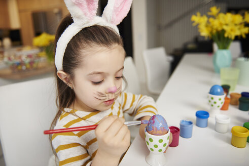 Girl with bunny ears sitting at table painting Easter eggs - ABIF00169