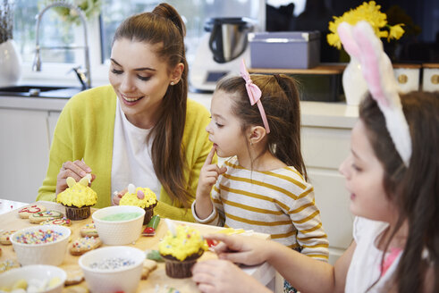 Mother with daughters decorating Easter cookies and muffins in kitchen - ABIF00178