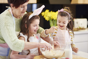 Grandmother and granddaughters baking Easter cookies in kitchen together - ABIF00181
