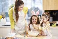 Happy mother and daughters baking Easter cookies in kitchen together - ABIF00184