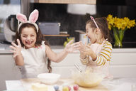 Two playful sisters having fun baking Easter cookies in kitchen together - ABIF00187