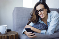 Woman using mobile phone while lying on sofa at home - CAVF16326
