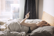 Woman using smart phone while lying on bed - CAVF16404