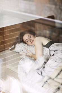 Smiling woman sleeping on bed at home seen through glass - CAVF16407