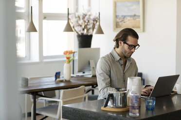 Confident man using laptop computer at home - CAVF16509