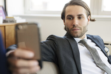 Businessman using mobile phone while sitting on sofa at home - CAVF16524