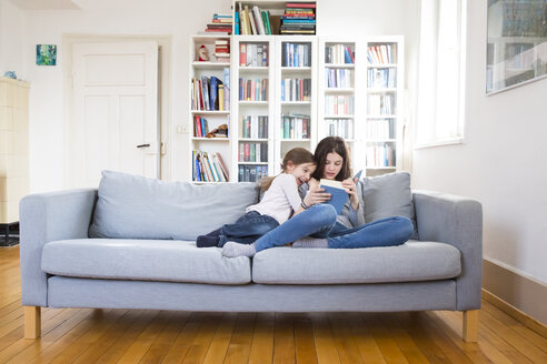 Sisters sitting on couch, reading book - LVF06812