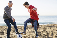 Playful father and son playing soccer at beach against clear sky - CAVF16588