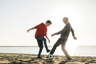 Full length of father and son playing soccer at beach against clear sky - CAVF16591