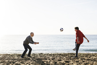 Playful son kicking soccer ball while father defending at beach against clear sky - CAVF16594