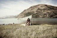 Woman using phone while sitting under shade at seashore - CAVF16618