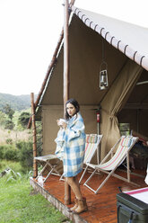 Woman wrapped in towel drinking coffee while standing at tent during vacation - CAVF16684