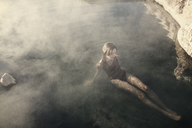 High angle view of woman sitting in water at Mammoth Lake Hot Springs - CAVF16708
