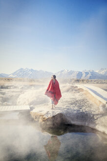 Woman wrapped in blanket standing on rock at Mammoth Lake Hot Springs - CAVF16711