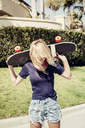 Woman carrying skateboard on shoulders at footpath - CAVF16747