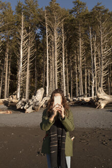 Young woman photographing through smart phone against trees on beach - CAVF16768