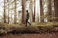 Side view of woman walking on fallen tree in forest - CAVF16777