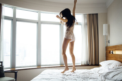 Full length of cheerful woman jumping on bed in hotel room in lingerie - CAVF16780