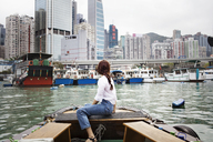 Side view of female tourist looking at buildings by sitting on boat - CAVF16786